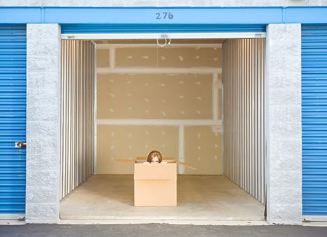 Girl inside cardboard box, large showing storage unit with blue doors