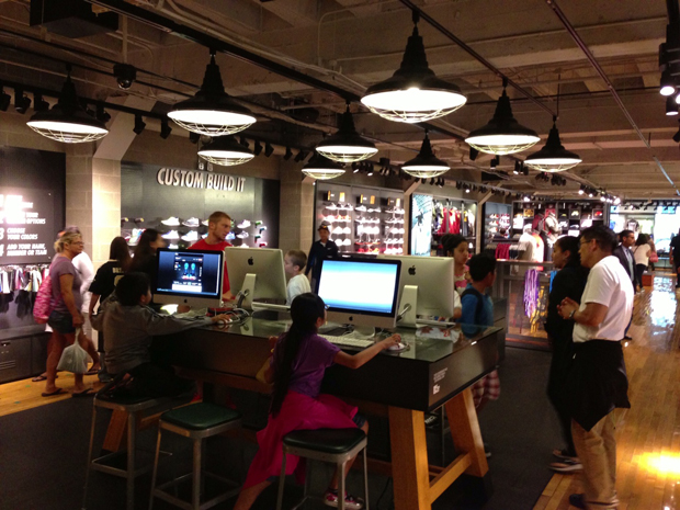 """Nike store featuring a """"custom build it"""" shoe category as well as a kids computer play area."""