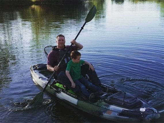 A father and son share time in the kayak (near the shore).