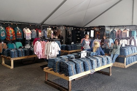 Workers take a break after merchandising a tent at an on-site store. They know from experience that jeans stacked on a table will sell better than hanging on a rack.