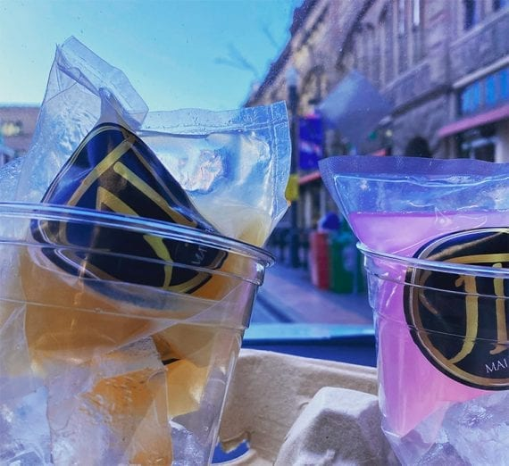 A bagged Mai Tai and rosewater gimlet sitting in ice on the dashboard of a car.