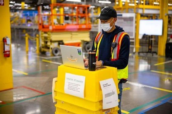 La pandémie a modifié les opérations, y compris les retours de produits, pour de nombreux commerçants en ligne. Ici, un employé d'un centre de traitement des commandes d'Amazon porte un masque.