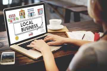"""Photo a a lady typing on a laptop screen that says """"Shop local"""""""