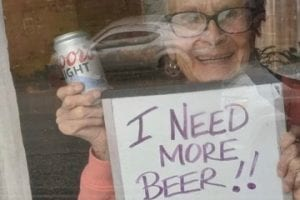 "Photo of a 93-year-old lady holding ""I Need a Beer"" sign"