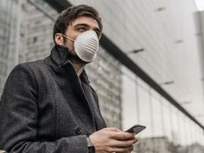 Man wearing a mask holding a smartphone