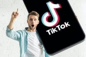 Photo of a young male holding a smartphone with TikTok app on it