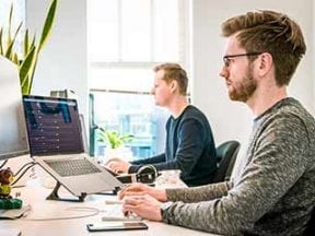 Image of two male digital workers in front of computer screens