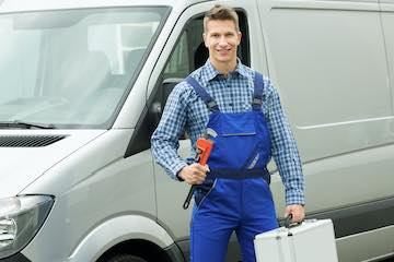 Photo of a plumber in front a van holding a pipe wrench