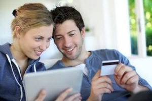 Image of a young married couple shopping on a computer