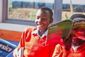 Photo of a boy from Tanzania laughing and holding a book