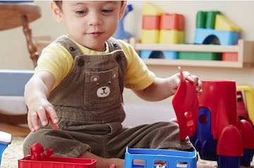 Partial screenshot from Green Toys home page, showing a child playing with toys