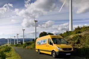 Image of a DHL delivery truck driving beneath windmills on a road
