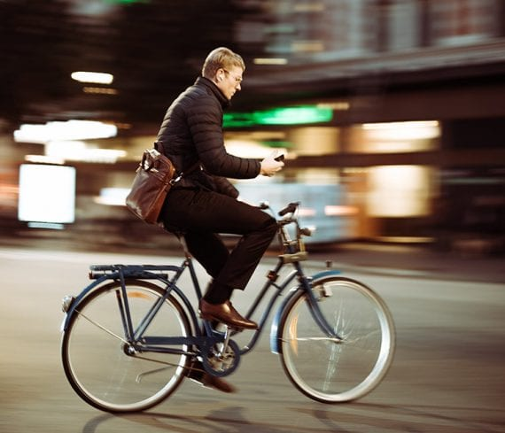 Photo of a man riding a bike in an urban setting