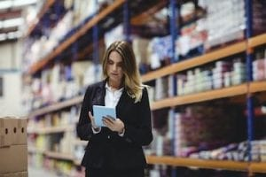 Photo of female in a warehouse holding a tablet