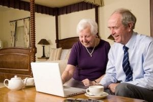 Image of an older man and woman shopping on a computer