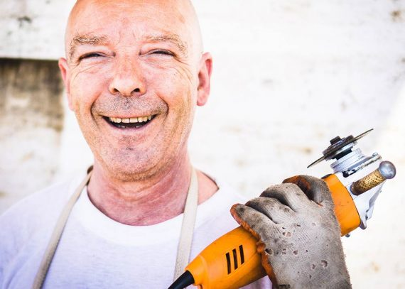 Photo of a smiling older male holding a power tool