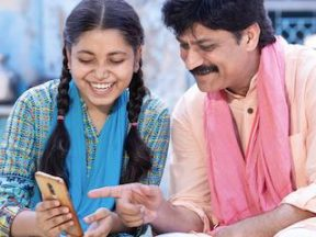 Photo of an Indian man and teenage daughter looking at a smartphone