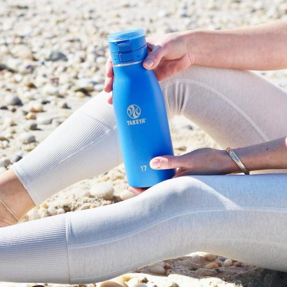 Image of a lady on a beach sitting, holding a blue water bottle. Lines can lead directly to a product and then terminate, such as the women's legs and her arms, which lead to the water bottle. Source: TakeyaUSA.com.