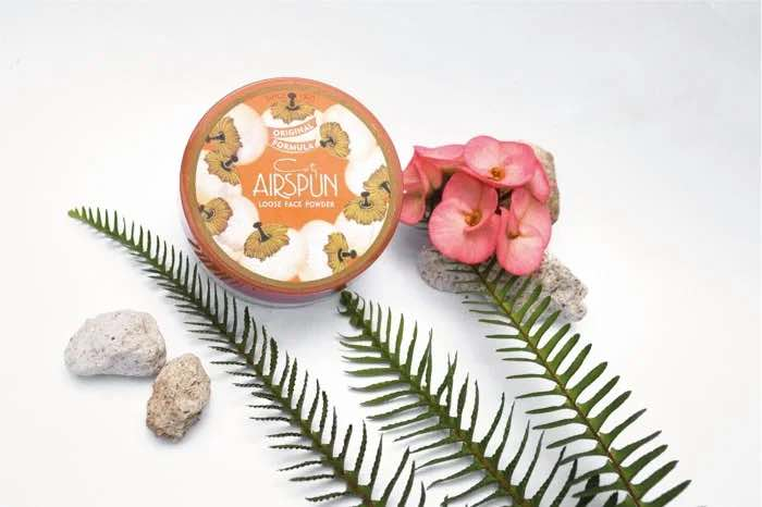 Photo sample from ExpertPhotography.com focusing on face powder with supporting plants and rocks.